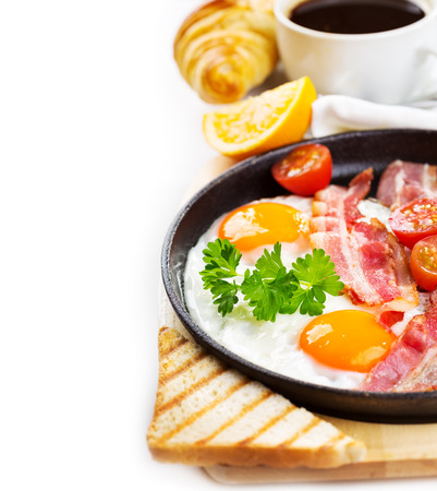 bacon and eggs: pan of fried eggs, bacon and vegetables on white background