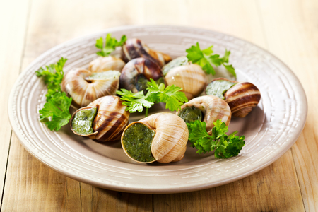 plate of escargots on wooden table
