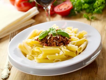 bord penne pasta met bolognese saus op houten tafel