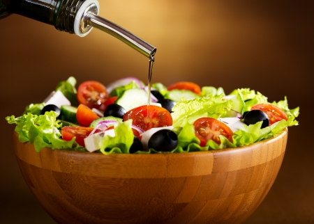 greek salad: oil pouring into bowl of greek salad Stock Photo