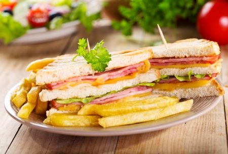 jamon y queso: sándwiches con patatas fritas en la mesa de madera