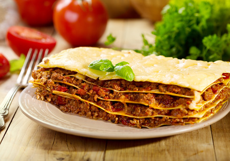 lasagna: plate of lasagna on wooden table
