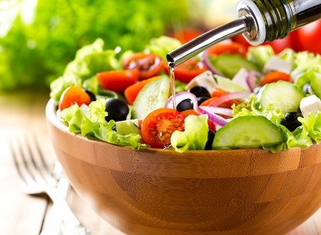 green salad: oil pouring into bowl of  salad