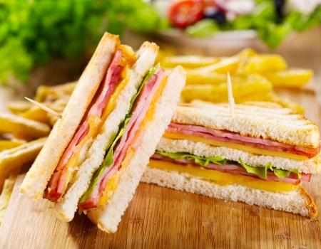 club sandwiches met frieten op een houten tafel