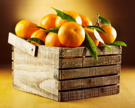 fresh tangerines with leaves in wooden box photo