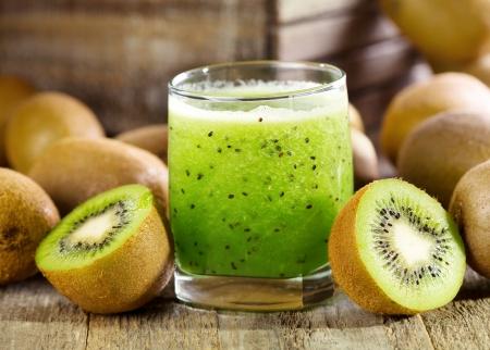 Glas Kiwi-Saft mit frischen Früchten auf Holztisch Lizenzfreie Bilder