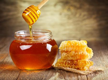 Barattolo di miele con nido d'ape su tavola di legno Archivio Fotografico - 26015645