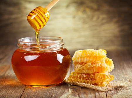 honeycomb: tarro de miel con panal en la mesa de madera