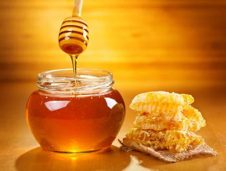honey pot: jar of honey with honeycomb on wooden table Stock Photo