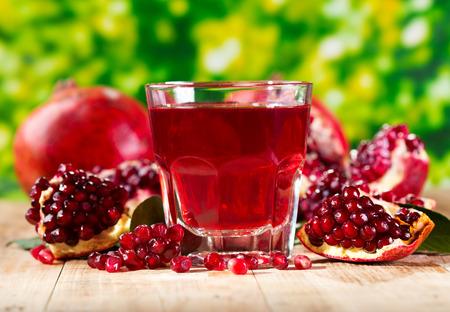 나무 테이블에 신선한 과일 석류 주스의 유리