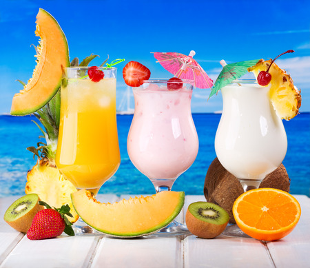 tropical cocktails with fresh fruits on a beach photo