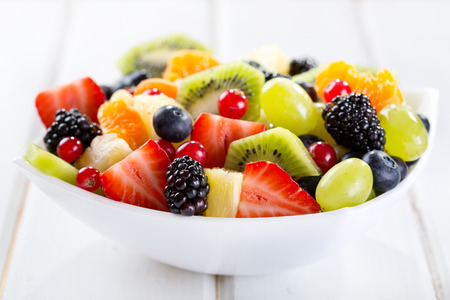bowl of fruit salad on wooden table photo