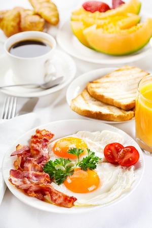 기름에 튀긴 된 계란, 커피, 오렌지 주스, 크루아상, 토스트와 과일과 함께 아침 식사