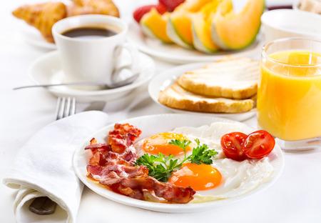 Ontbijt met gebakken eieren, koffie, jus d'orange, croissants, toast en fruit Stockfoto