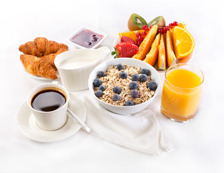 continental breakfast: healthy breakfast with bowl of muesli, coffee, croissants, juice and fruits Stock Photo