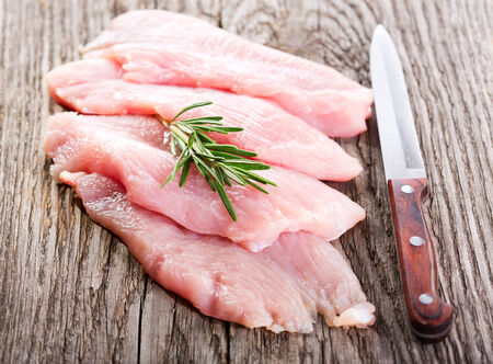 raw chicken breast fillets with rosemary on wooden table