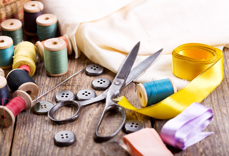 vestidos antiguos: Antiguas tijeras, botones, hilos en una mesa de madera