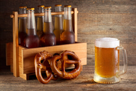 mug of beer with bottles in wooden box photo