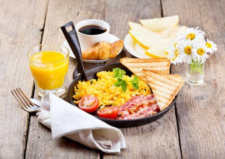 healthy breakfast with scrambled eggs, juice and fruits on wooden background photo