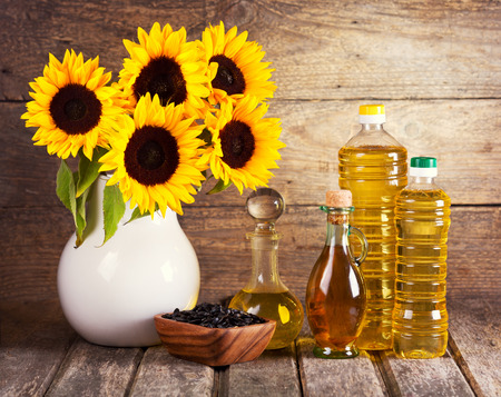still life with sunflower oil and flowers photo