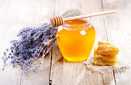 jar of honey with honeycomb and lavander flowers on wooden table Stock Photo