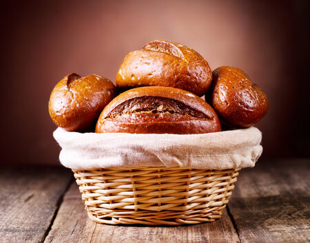 bread rolls: bread in wicker basket on wooden background