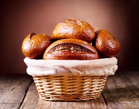 canasta de pan: pan en cesta de mimbre sobre fondo de madera