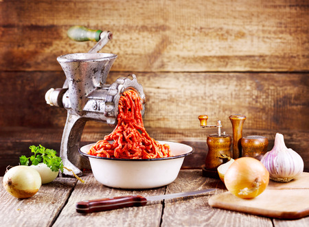 minced meat: old grinder with minced meat on wooden table