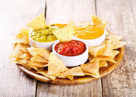 nacho's met verschillende sauzen op houten tafel Stockfoto