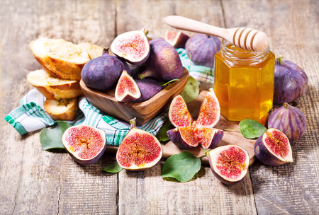 fresh figs with jar of honey on wooden table photo