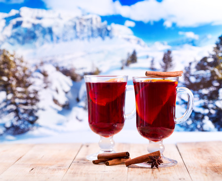 glasses of mulled wine on wooden table over winter landscape