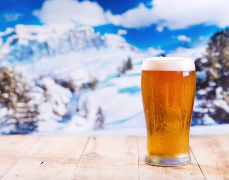 Glas Bier auf Holztisch über Winterlandschaft