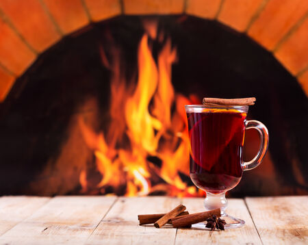 glass of mulled wine on wooden table over fireplace photo