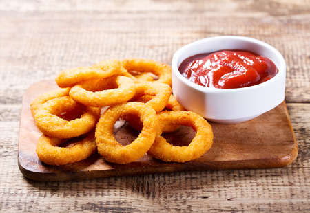 onion rings with ketchup on wooden board