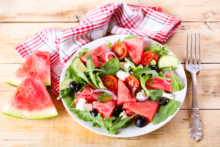 salads: plate of watermelon salad on wooden table
