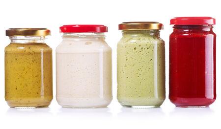 horseradish: jars of preserved mustard, ketchup, horseradish isolated on white background