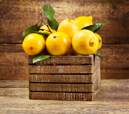 fresh lemons with leaf in wooden box photo