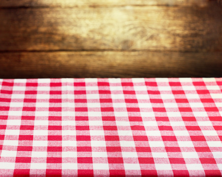 red tablecloth: Checkered red tablecloth over rustic wooden background