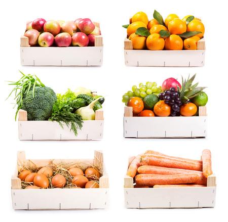 set van verschillende voedingsmiddelen in houten doos op een witte achtergrond