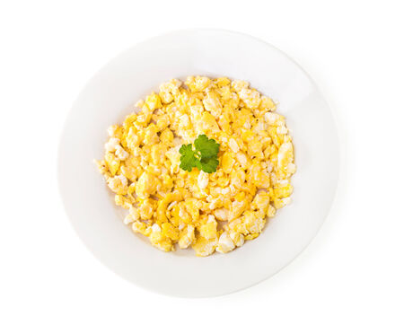 scrambled eggs: plate of scrambled eggs with parsley on white background