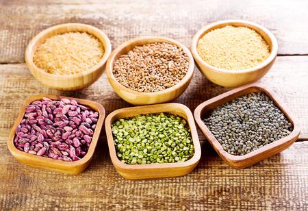 lentejas: varios ingredientes alimentarios en un tazones sobre la mesa de madera