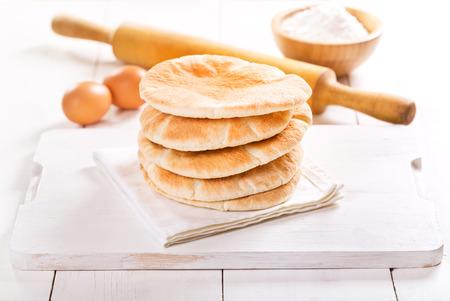pita: pita bread on wooden board