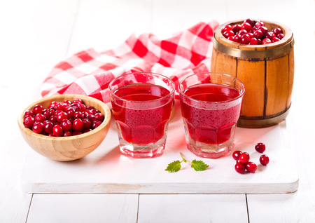 cranberry: glasses of cranberry juice with fresh berries on wooden table
