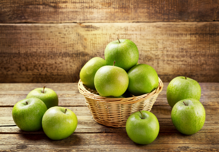 fresh green apples on wooden table photo