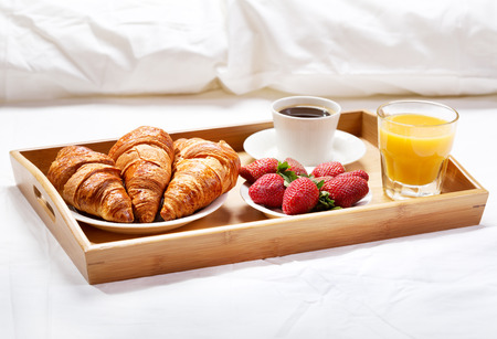 breakfast in bed: breakfast in bed with coffee, croissants, strawberries and juice Stock Photo