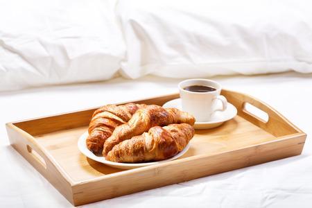 ontbijt op bed met koffie en croissants Stockfoto