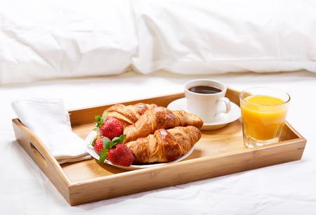 Frühstück im Bett mit Kaffee, Croissants, Erdbeeren und Saft Standard-Bild