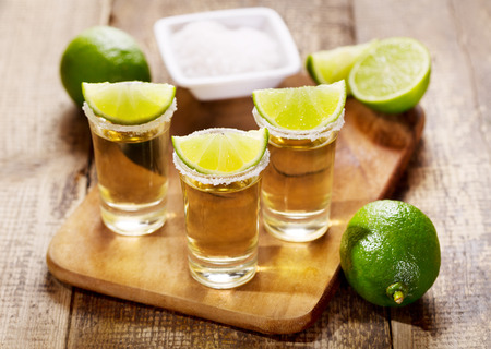 glasses of tequila with lime on wooden table