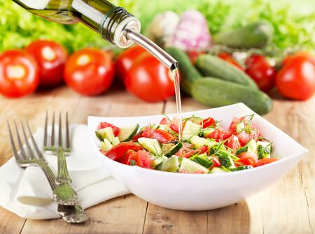 Öl in Schüssel Gemüse-Salat gießen