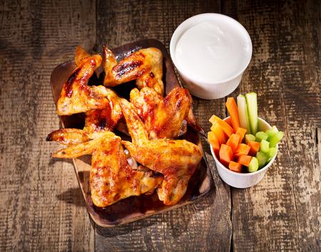 carne de pollo: alitas de pollo con verduras frescas y salsa de mesa de madera